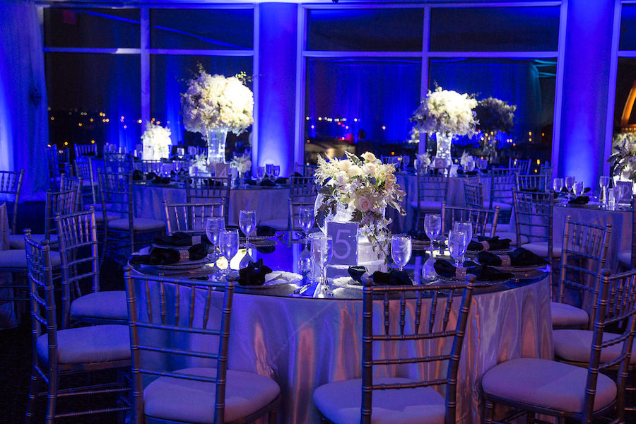 Indoor, Winter Wonderland Wedding Reception Decor with Blue Uplighting and Tall Ivory Table Centerpieces with Pinspotting | Tampa Wedding Planner UNIQUE Weddings and Events