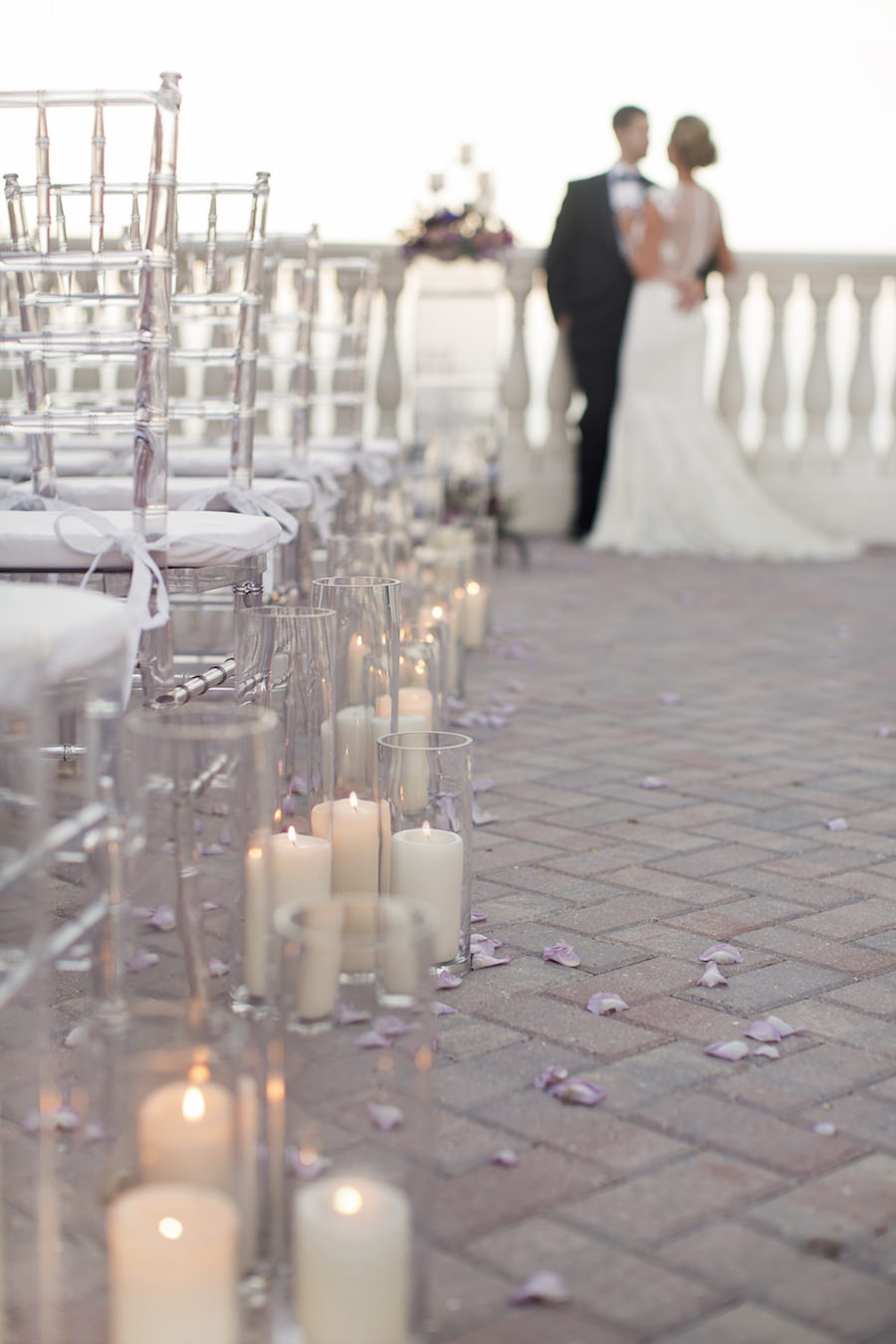 Candlelit Ceremony Aisle with Purple Rose Petals and Clear Chiavari Chairs | Clearwater Beach Wedding Venue Hyatt Regency | Wedding Planner Special Moments Event Planning | Chair Rentals Gabro Event Services