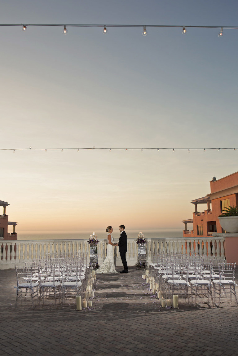 Sunset Candlelit Ceremony Aisle with Purple Rose Petals and Clear Chiavari Chairs | Clearwater Beach Wedding Venue Hyatt Regency | Wedding Planner Special Moments Event Planning | Chair Rentals Gabro Event Services | Djamel Photography