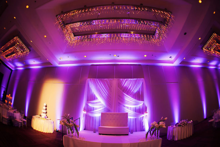 Elegant Glamorous Ballroom Wedding Reception Decor with White Drapery Backdrop, Purple Uplighting, and Ivory Floral Centerpieces | Tampa Wedding Venue Hilton Downtown