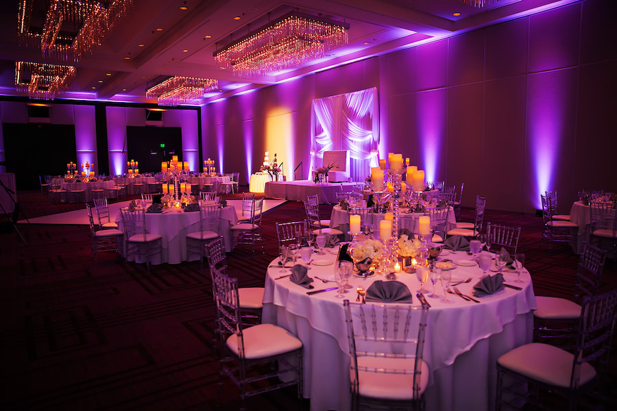 Elegant Wedding Reception Decor with White Drapery Backdrop, Purple Uplighting, and Ivory Floral Centerpieces and Candelabras and Clear Chiavari Chairs | Limelight Photography | Tampa Wedding Venue Hilton Downtown