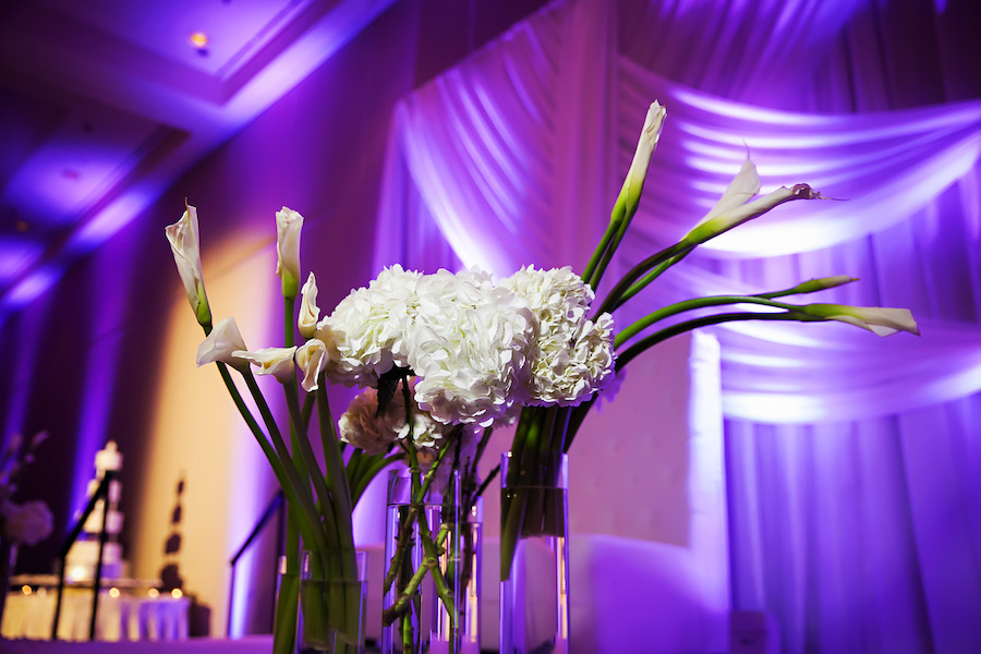 White Floral Centerpieces and Stems at Elegant Ballroom Wedding Reception with White Drapery Backdrop, Purple Uplighting | Limelight Photography | Tampa Wedding Venue Hilton Downtown