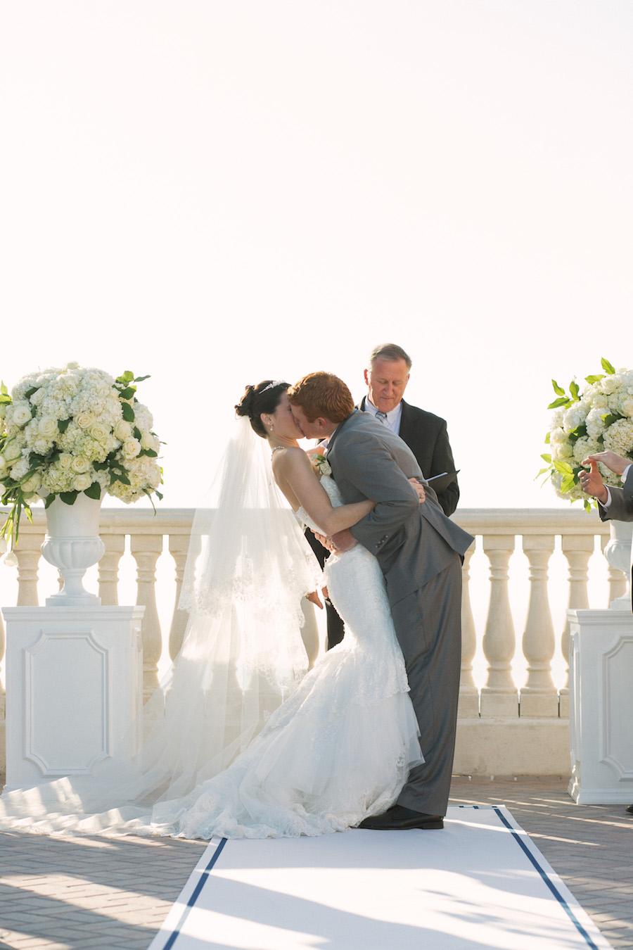 Bride and Groom Wedding Ceremony Kiss   Classic, Elegant White Wedding Ceremony Decor Flowers on Pedestal   Clearwater Beach Hotel Wedding Venue   Hyatt Regency Clearwater Sky Terrace Outdoor Ceremony