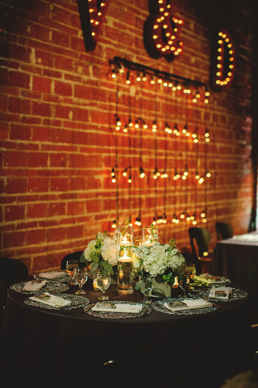 Silver and Ivory Wedding Reception Decor Centerpieces with Floating Candles, Silver Chargers and Exposed Brick Walls with Hanging String Lights | St. Petersburg Wedding Venue NOVA 535 | Signature Event Rentals | Wedding Planner Special Moments Event Planning | Iza's Flowers