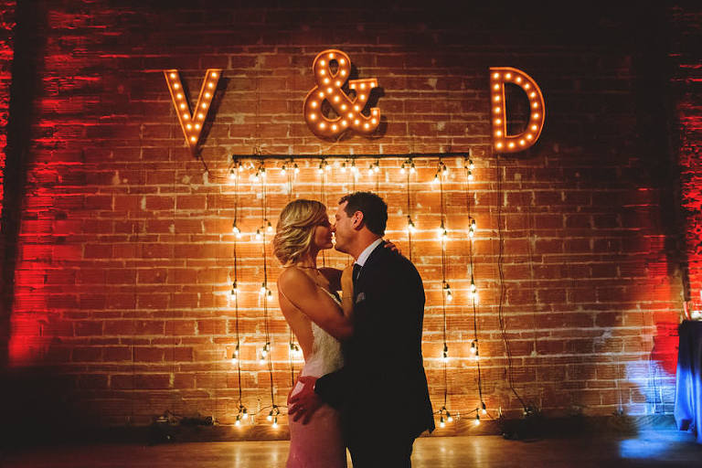 Bride and Groom Wedding Portrait with Lighted Marquee Monogram Letters, Exposed Brick and Industrial String Lights | Modern Industrial Wedding Reception Decor Inspiration | Downtown St. Petersburg Wedding Venue NOVA 535 | Special Moments Event Planning