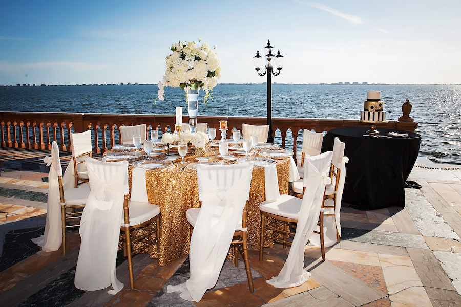 Gold Sequined Linens with Chiavari Chairs in White Draped Chair Covers and Tall Centerpieces | Outdoor Waterfront Wedding Reception | Historic Sarasota Wedding Venue Ringling Museum - Ca'd'Zan Mansion | Limelight Photography | Wedding Planner NK Productions