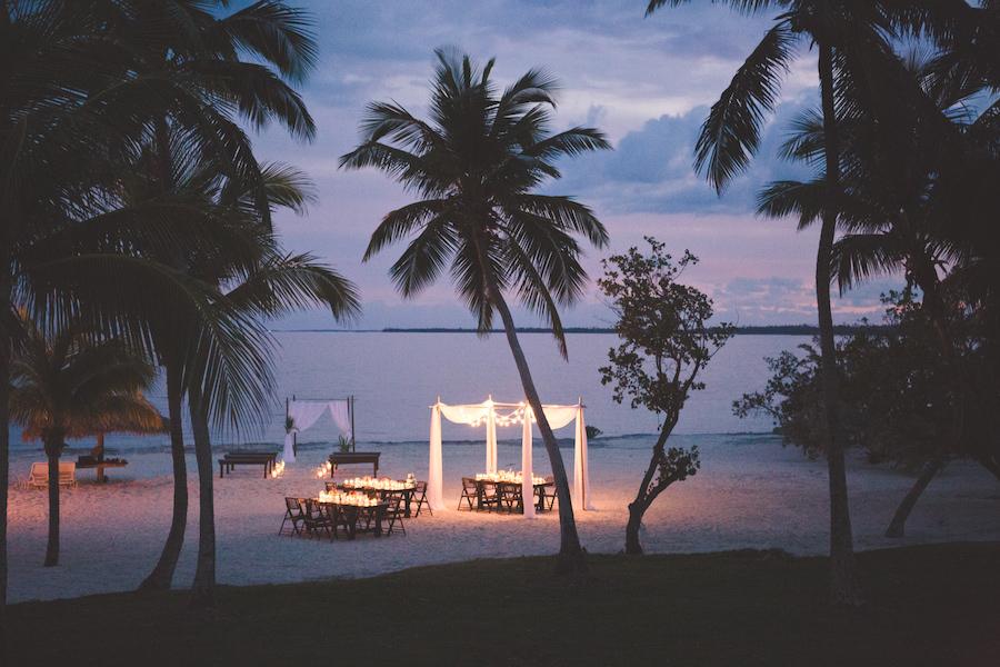 Bahamas Destination Beach Caribbean Reception Venue with Farm Tables, Bamboo Seating and Candlelight | Aisle Society Weddings Abaco Beach Resort