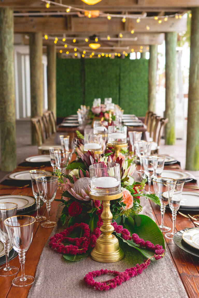 Oceanfront Tampa Bay Wedding Reception Decor with Wooden Feasting Tables, Gold Rimmed Dishes, Floating Candles and Tropical Floral Centerpieces | Waterfront Wedding Venue Hilton Clearwater Beach | Rentals A Chair Affair