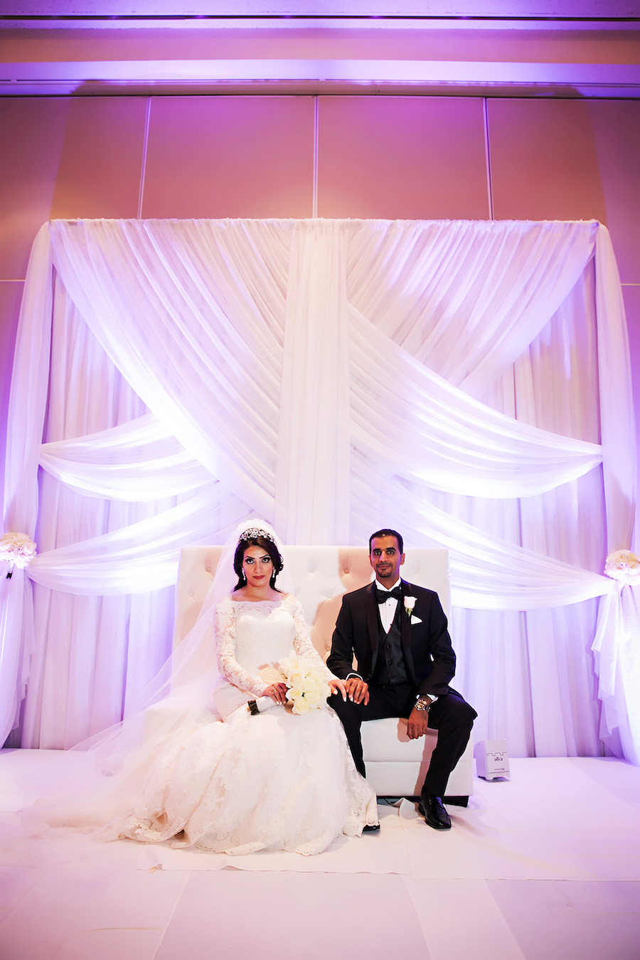 Elegant Indian Bride and Groom Ballroom Wedding Portrait with White Drapery Backdrop and Purple Uplighting | Downtown Tampa Hotel Wedding Venue Hilton Downtown | Wedding Photographer Limelight Photography