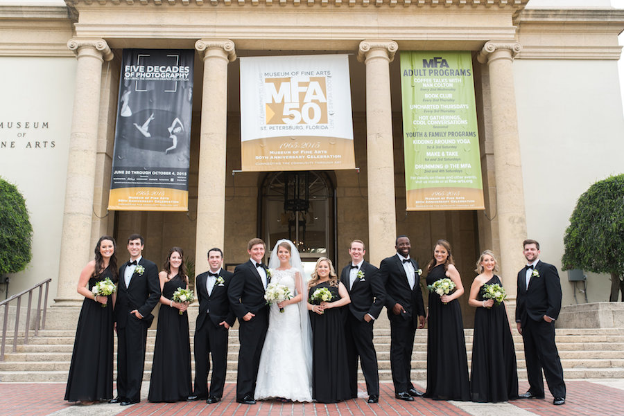 Outdoor Bridal Party Wedding Portrait at Downtown St. Pete Wedding Venue Museum of Fine Arts | Black Bridesmaid Wedding Gowns with Cap Sleeve Lace Alfred Angelo Wedding Dress and Ivory Wedding Bouquet | St. Petersburg Wedding Photographer Caroline and Evan Photography