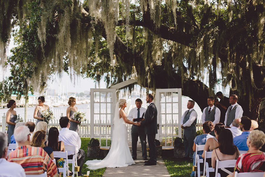 Vintage Outdoor Wedding Ceremony under Spanish Moss Tree with White Resin Folding Chairs and White French Door Arched Doorway Altar | Sarasota Rentals by Reserve Vintage Rentals | Waterfront Sarasota Wedding Venue Palmetto Riverside Bed and Breakfast