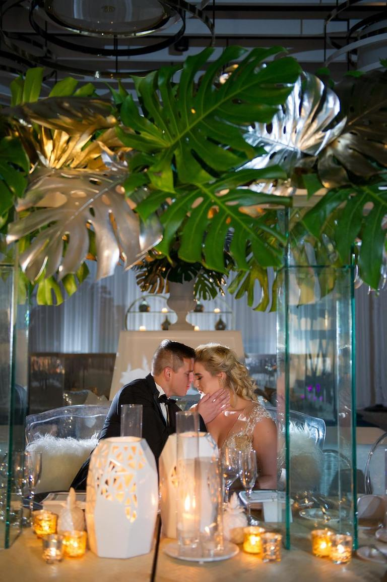 Modern Gold South Beach Inspired Wedding Reception Decor with Tall Palm Leaf Centerpieces, Candles and Gold Linens from Over the Top Linen Rentals | Clearwater Beach Wedding Venue Wyndham Grand | Wedding Planner Parties a la Carte | Andi Diamond Photography