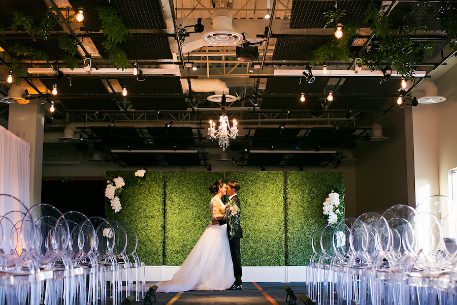 Modern Greenery Inspired Wedding Ceremony with Grass Wall, Chandelier and Ghost Chairs   Downtown Tampa Rooftop Wedding Venue The Glazer Children's Museum   Bridal Wedding Dress Shop Isabel O'Neil Bridal   Wedding Photographer Limelight Photography   Lighting Rental Nature Coast Entertainment Services   Furniture and Chair Rentals A Chair Affair