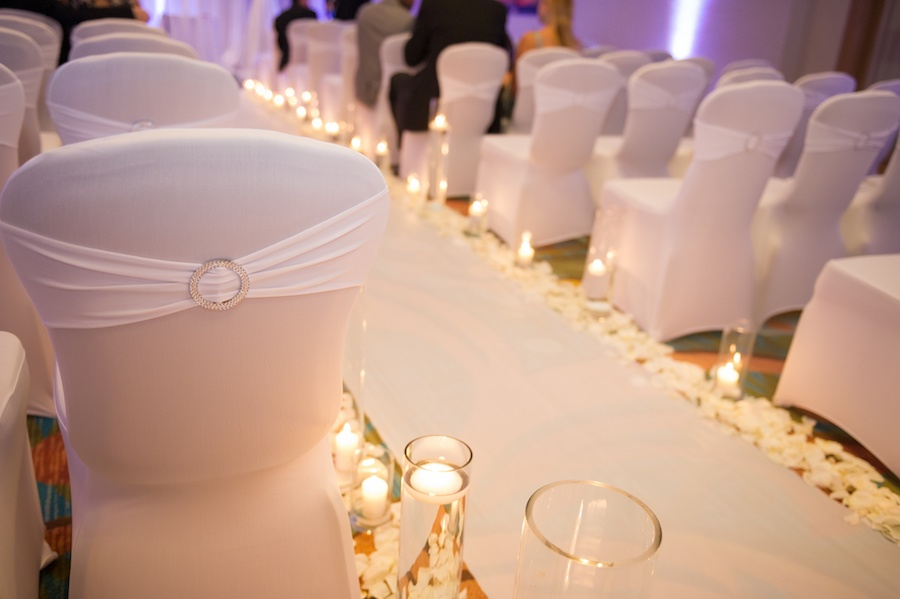 Elegant, Modern White Wedding Ceremony Seating with Candlelit Aisle and White Rose Petals