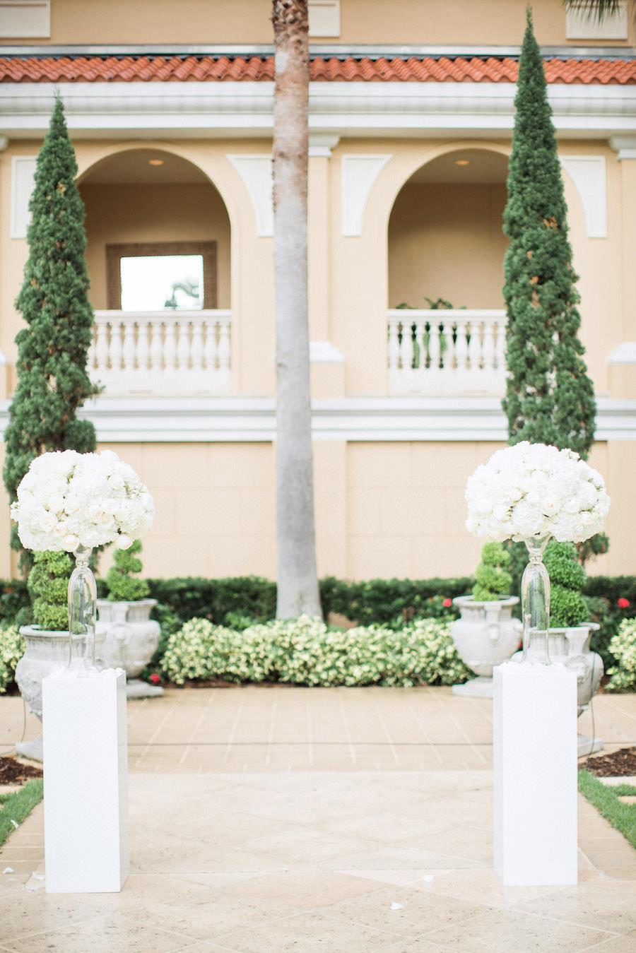 Elegant, Outdoor Wedding Ceremony with Tall White Centerpieces on White Pedestals   Sarasota Hotel Garden Wedding Venue Ritz Carlton