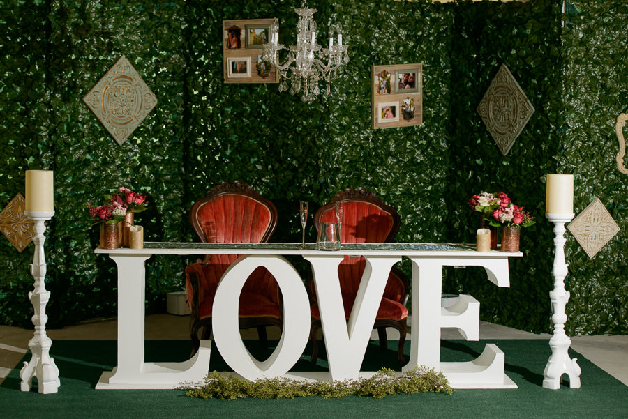 Spring Hill Wedding Reception Decor with Love Sweetheart Table, Red Velvet Chairs, and Red Floral Centerpieces