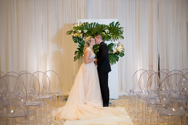 Ballroom Wedding Ceremony with Draping by Gabro Event Services, Ghost Chairs from A Chair Affair and Palm Leaf Ceremony Altar Backdrop | Hotel Wedding Venue Wyndham Grand Clearwater Beach | Andi Diamond Photography | Wedding Planner Parties a la Carte