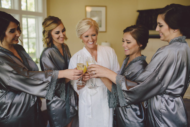 Bride and Bridesmaids Getting Ready Portriat in Grey Satin Robes Toasting with Mimosas