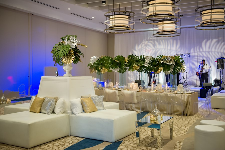 Modern White & Gold South Beach Inspired Wedding Reception Decor with Lounge White Furniture, Ghost Chairs and Tall Palm Leaf Centerpieces | Clearwater Beach Wedding Venue Wyndham Grand | Wedding Planner Parties a la Carte