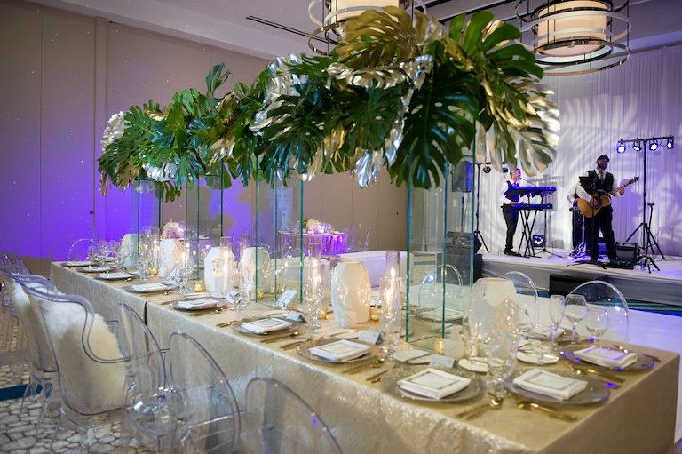 Modern Gold South Beach Inspired Wedding Reception Decor with Ghost Chairs from A Chair Affair, Tall Palm Leaf Centerpieces and Gold Linens from Over the Top Linen Rentals | Clearwater Beach Wedding Venue Wyndham Grand | Wedding Planner Parties a la Carte