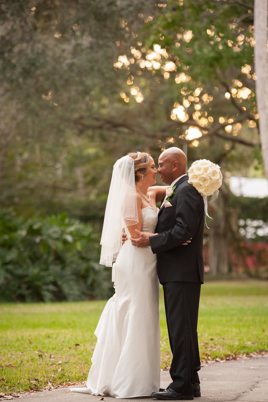 Outdoor, Bride and Groom Wedding Portrait in Strapless, Beaded Ivory Wedding Dress and Black Groom's Suit