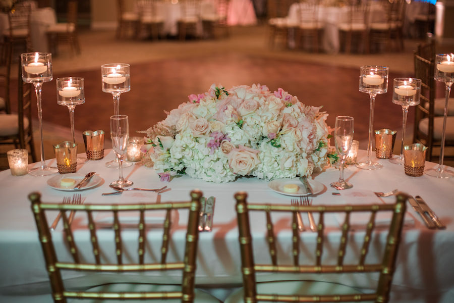 Sweetheart Table White Hydrangea and Blush Pink Rose Centerpiece Flowers with Tall Candles and Gold Chiavari Chairs | Wedding Reception Decor