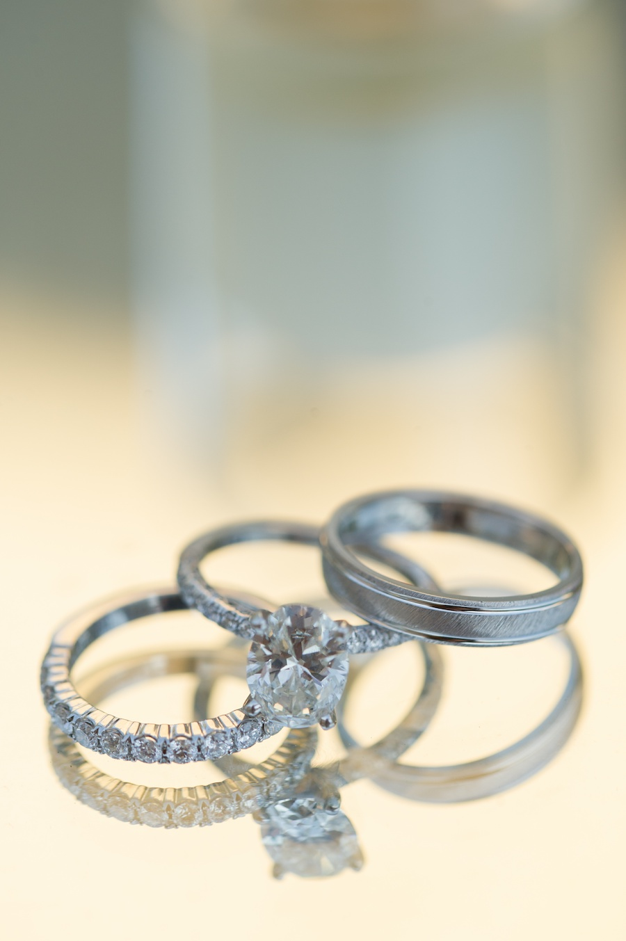 Bride and Groom Wedding Ring and Engagement Ring Detail with Reflection