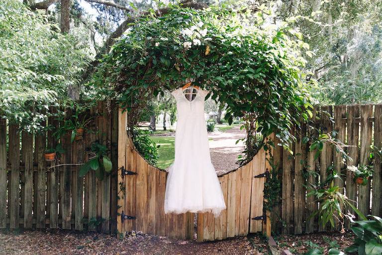 White, Beaded Lace Wedding Dress in Hanging in Rustic Woods