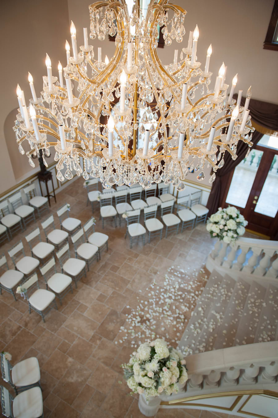 Indoor, Private Residence Wedding Ceremony with Silver Chiavari Chairs and Ivory Flower Petals and Elegant Chandelier