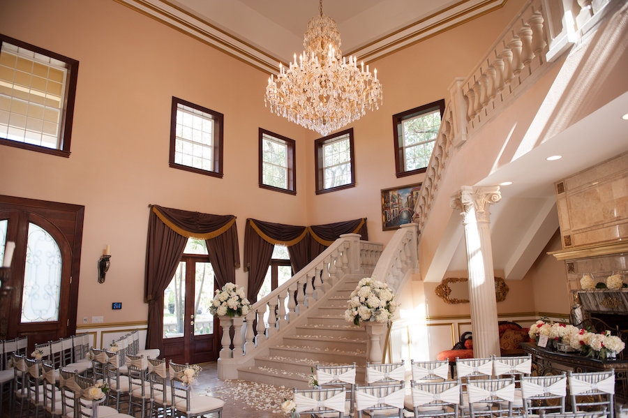 Indoor, Private Residence Wedding Ceremony with Silver Chiavari Chairs and Ivory Flower Petals and Elegant Chandelier over Staircase
