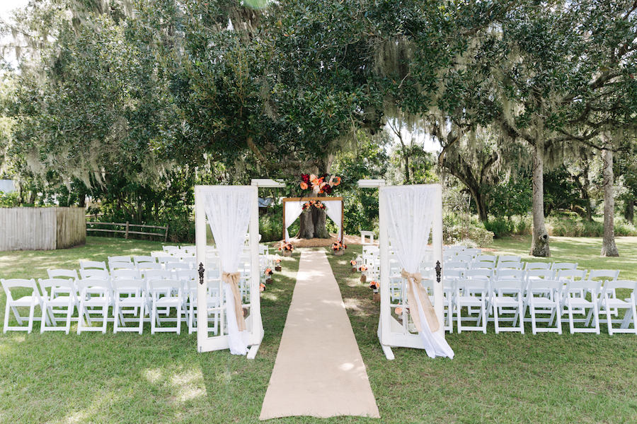 Outdoor Rustic Garden Wedding With Vintage Doors White Folding Chairs And Red Coral Floral Decor At Tampa Bay Venue Cross Creek Ranch