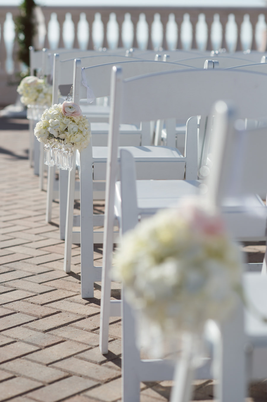 Wedding Ceremony White Resin Folding Chairs with Ivory Aisle Floral Arrangements | Clearwater Beach Wedding Planning Kimberly Hensley Events