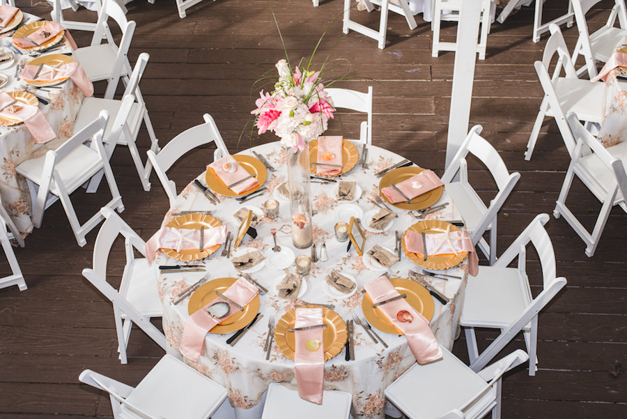 Ivory, Pink and Gold Floral Beach Inspired Wedding Reception Tables With Tall Pink Centerpieces, Satin Napkins and Gold Chargers   Wedding Tablescape Ideas & Inspiration   Outdoor Waterfront Hotel Wedding Venue Hilton Clearwater Beach   Rentals A Chair Affair