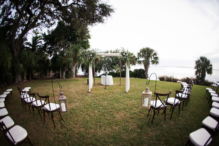 Outdoor, Sarasota Waterfront Wedding Ceremony with Brown and White Chairs, Lanterns and Arch   Tampa Bay Wedding Photographer Limelight Photography   Tampa Bay Wedding Planner NK Productions