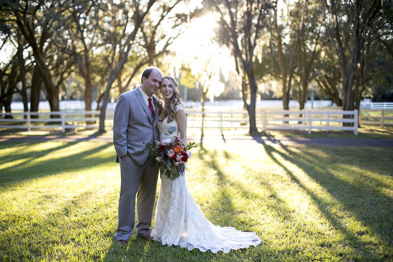 Bride and Groom Outdoor Southern Chic Wedding Portrait in Light Grey Suit and Burgundy Tie and Ivory Lace Allure Wedding Dress | Fall Themed Red Wedding Bouquet | Rustic Outdoor Wedding Tampa Bay Venue The Lange Farm