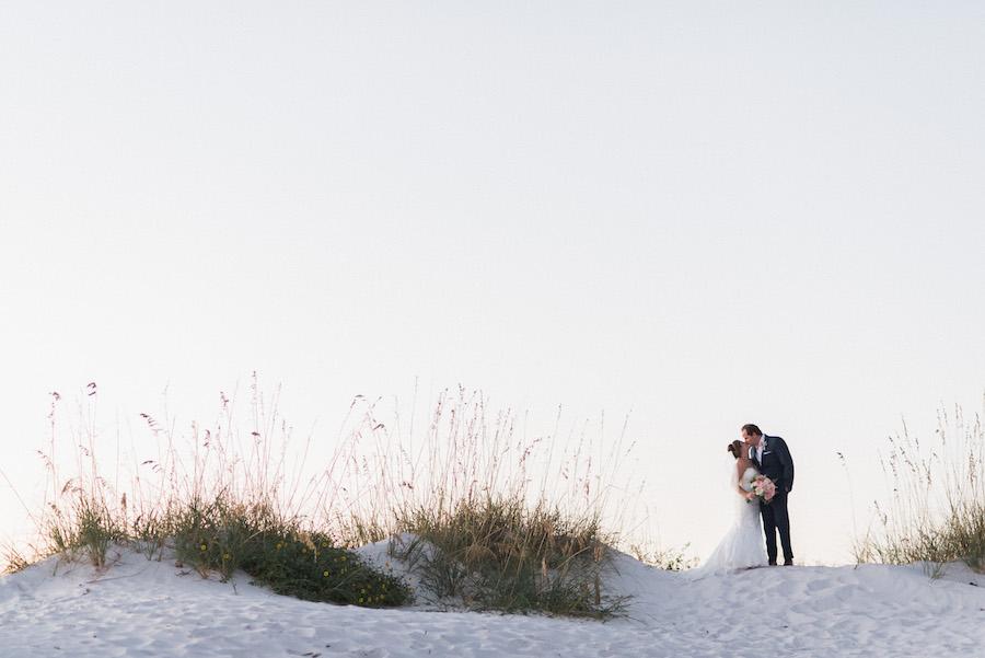 Florida Sunset beach wedding portrait | Bride and groom on sand dune with greenery | Tampa Bay Beachfront Hotel Wedding Venue Hilton Clearwater Beach