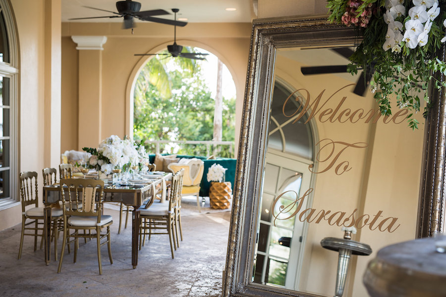 Outdoor Wedding Reception Ideas & Inspiration with Gold Chairs, White Centerpieces and Mirrored Calligraphy Welcome Sign | Sarasota Wedding Planner NK Productions
