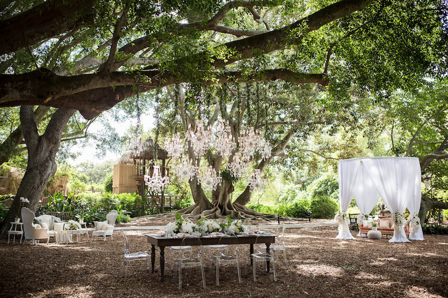 Elegant Garden Party Outdoor Wedding Reception with Chandelier Canopy, Ghost Chairs, Farm Chairs and Draped Vintage Lounge | Luxury Sarasota Wedding Venue Marie Selby Gardens | Wedding Planner NK Productions