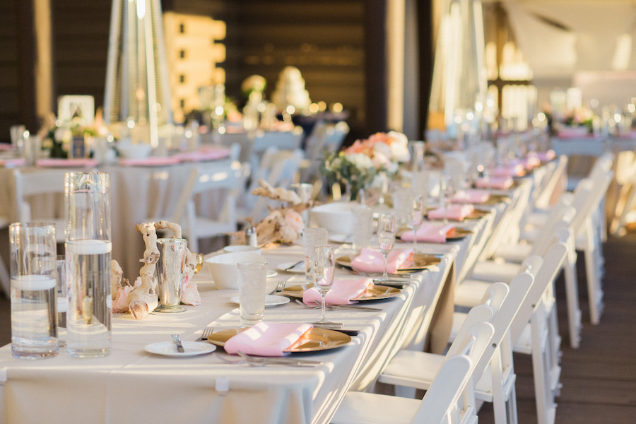 Romantic Elegant wedding reception decor with pink, peach and ivory floral centerpieces, Gold Chargers and Long Feasting Tables | Pink and white draping | Pink and white outdoor wedding reception | Tampa Bay Beachfront Hotel Wedding Venue Hilton Clearwater Beach