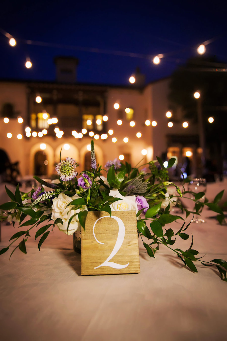 Ivory and Purple Flowers with Greenery Centerpieces and Rustic Table Number   Tampa Bay Wedding Photographer Limelight Photography   Tampa Bay Wedding Planner NK Productions