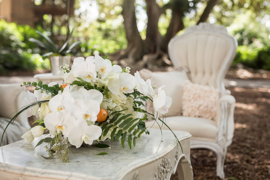 White Vintage Lounge with Tufted Velvet Couch and Chairs and Orchid and Orange Wedding Centerpieces