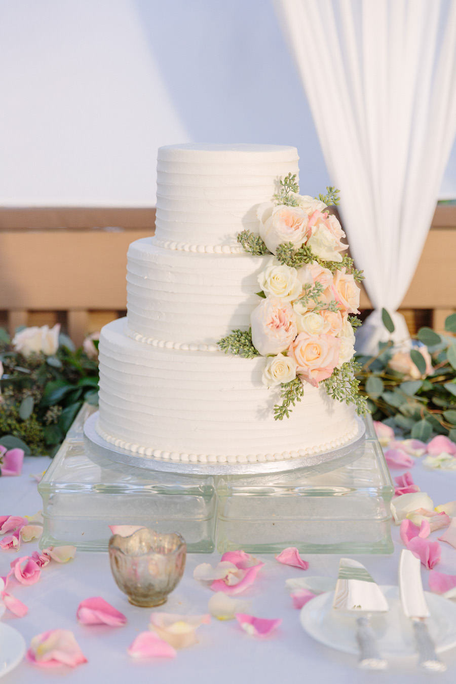 Three Tier Round White Wedding Cake with Real Blush and Ivory Ranunculus and Greenery on Clear Glass Cake Stand with Rose Petals