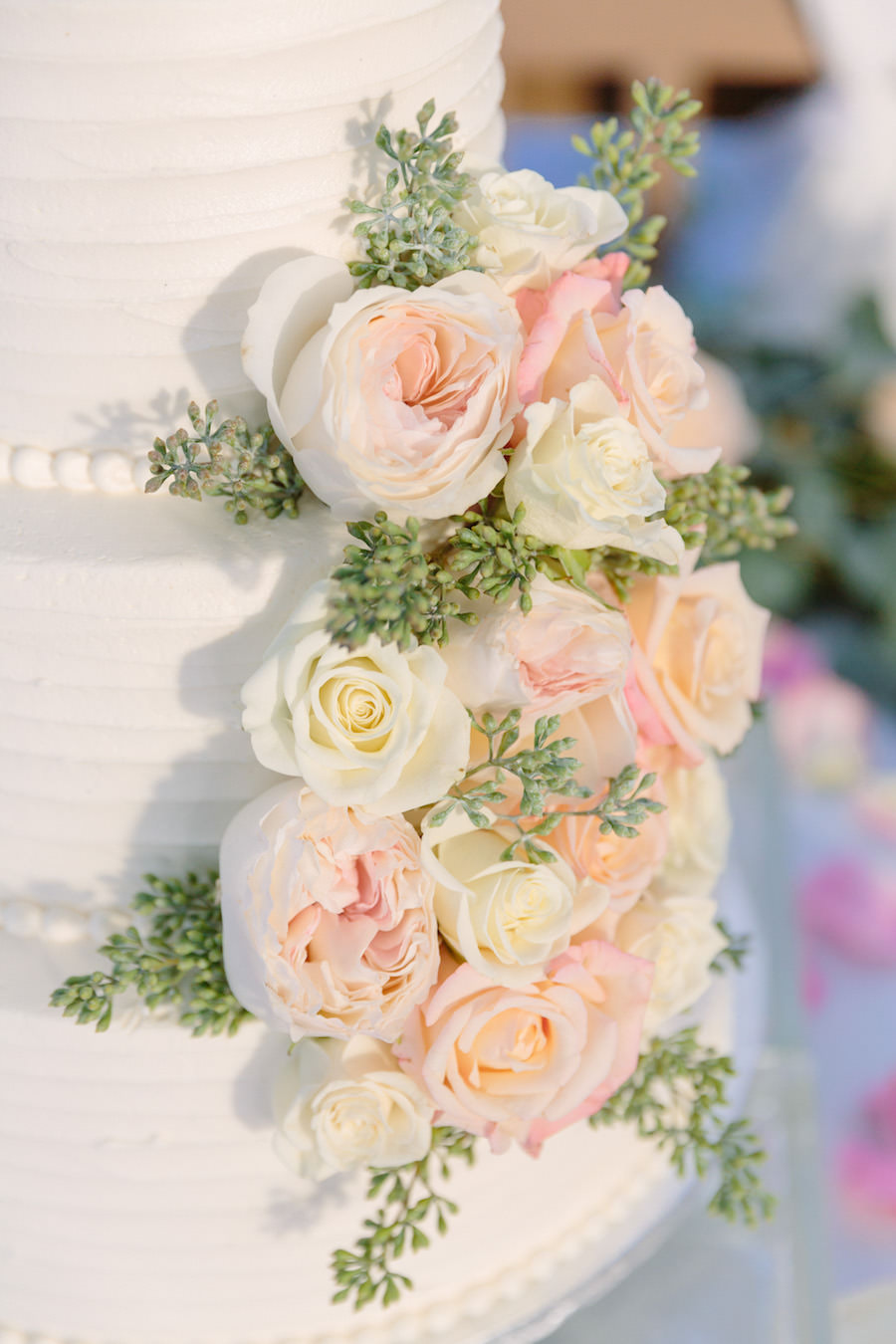 Three Tier White Wedding Cake with Real Blush and Ivory Ranunculus Flowers and Greenery
