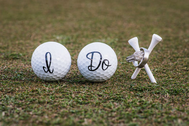 Diamond Engagement Ring and Band and Brushed Metal Wedding Band on Golf Tee with Golf Balls Saying I Do | Oldsmar Wedding Venue East Lake Woodlands Country Club