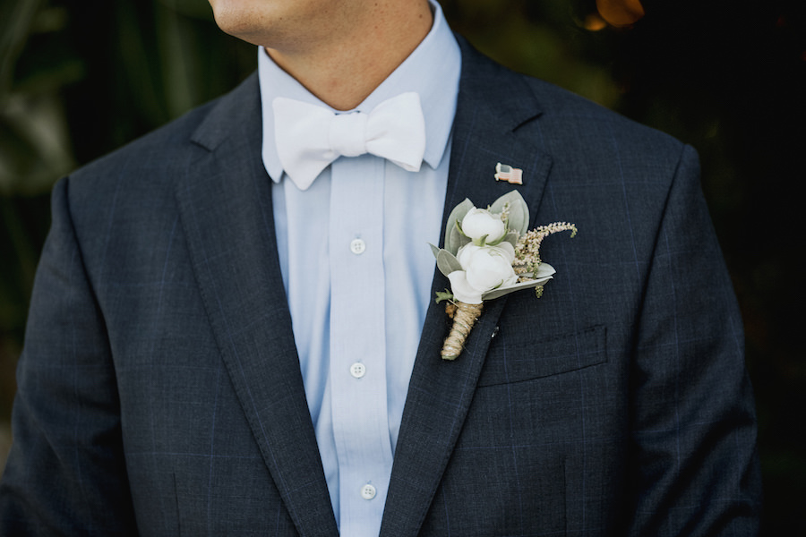 Groom in Navy Blue Suit and Powder Blue Button Up with White Bow Tie with Flag Pin and Ivory, Green and Burlap Boutonniere   Wedding Venue Sarasota Yacht Club   Tampa Bay Wedding Planner NK Productions