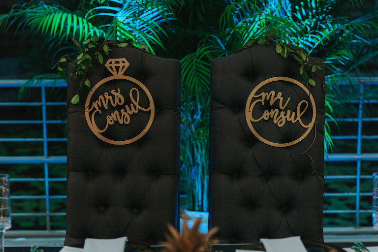 Black Tufted Wedding Sweetheart Chairs with Mr. and Mrs. Signs in Gold Cursive with Ring Outline | Tropical Modern Wedding Reception Decor and Inspiration