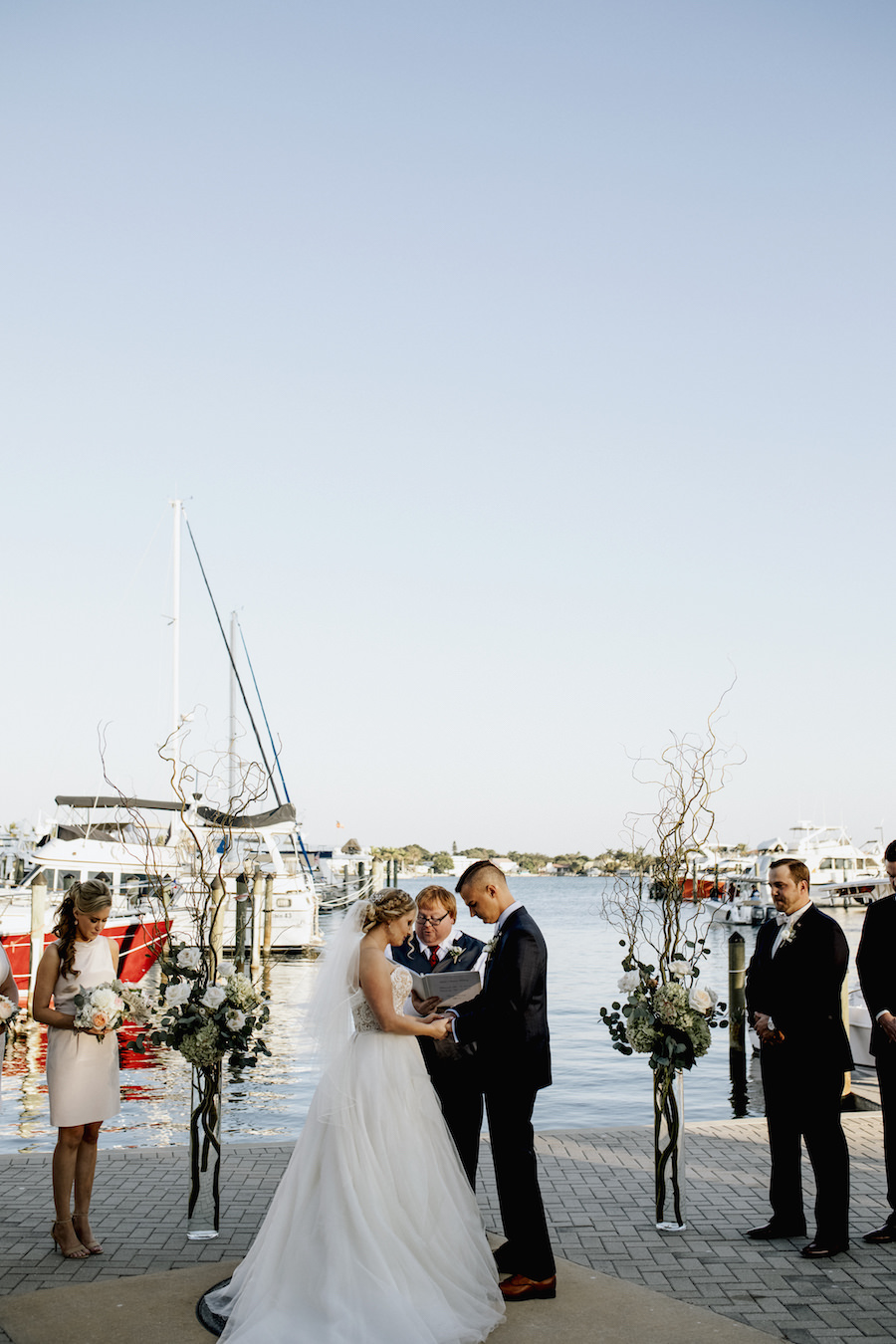 Outdoor Sarasota Wedding Ceremony with Bride and Groom Between Tall Glass Vases with Branches, Ivory Florals and Greenery   Wedding Venue Sarasota Yacht Club   Tampa Bay Wedding Planner NK Productions