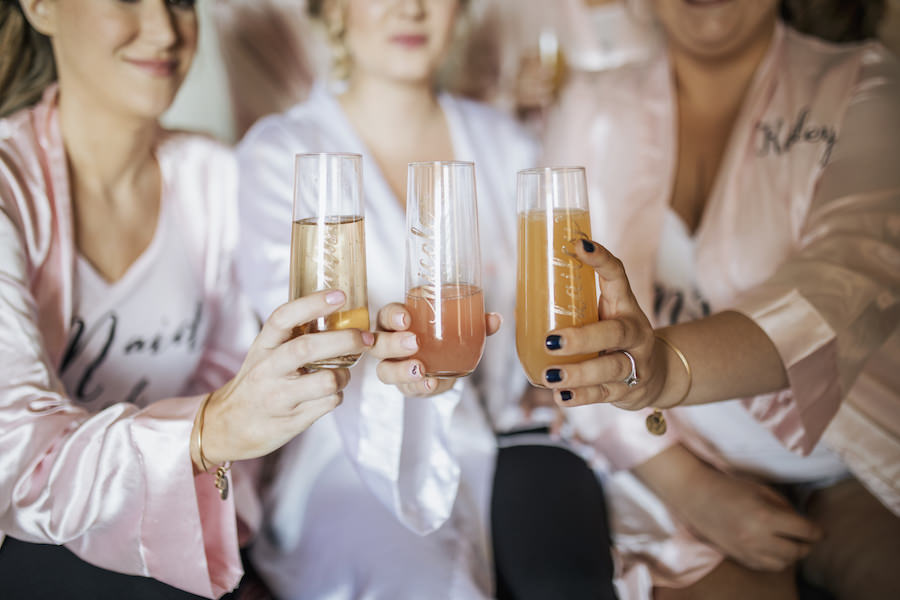 Bride and Bridesmaids Getting Ready with Mimosas in Personalized Stemless Champagne Flutes
