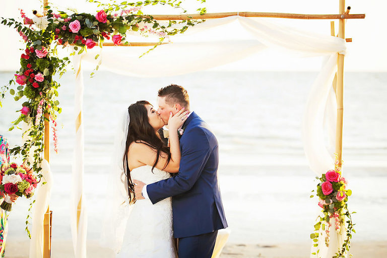 Tropical Beach Wedding Ceremony under Wooden Wedding Arch with White Tulle and Pink and Green Cascading Florals | Sarasota Wedding Photographer Limelight Photography