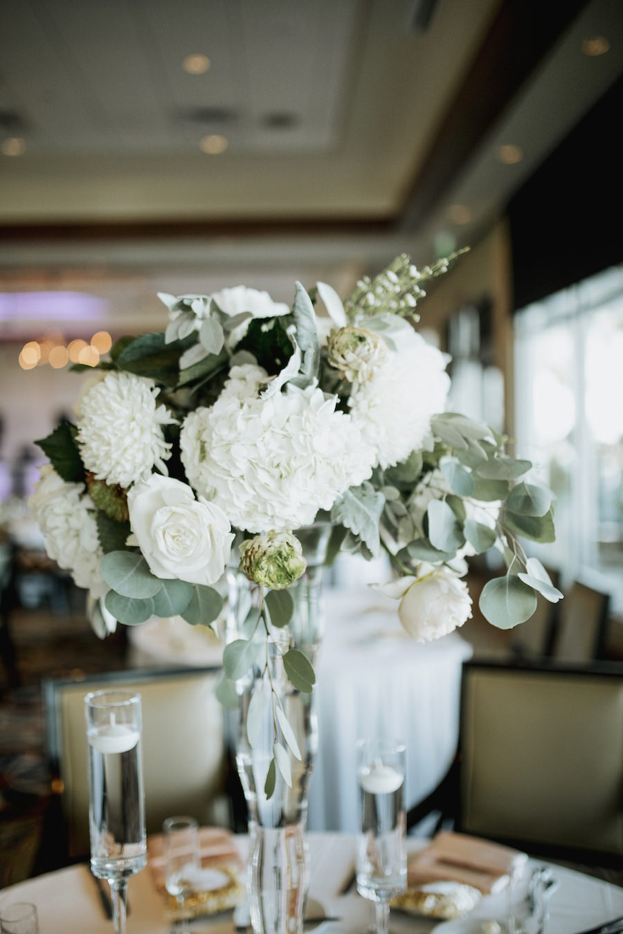Wedding Reception Centerpieces with Tall Glass Vase with White Flowers and Greenery and Short Glass Vases with White Floating Candles   Wedding Venue Sarasota Yacht Club   Tampa Bay Wedding Planner NK Productions